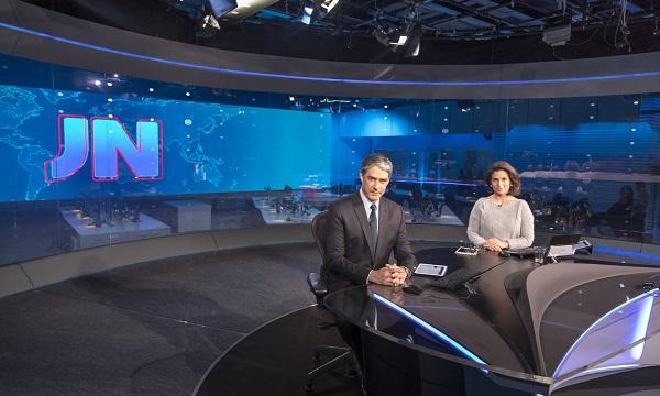 William Bonner e Renata Vasconcellos na bancada do Jornal Nacional. Ao fundo, em azul, um telão com as iniciais JN.